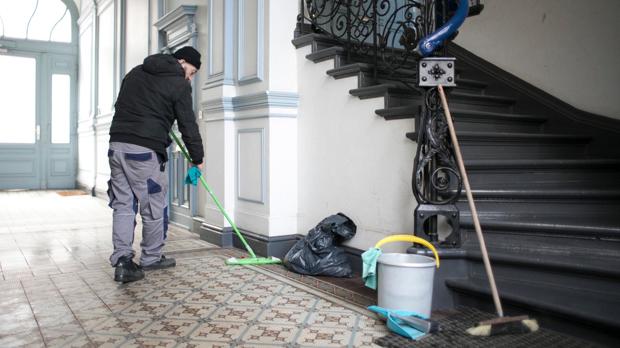 """""""ZDF.reportage: Wutsache - Mindestlohn"""": Ömer wischt den Boden in einem Hausflur."""